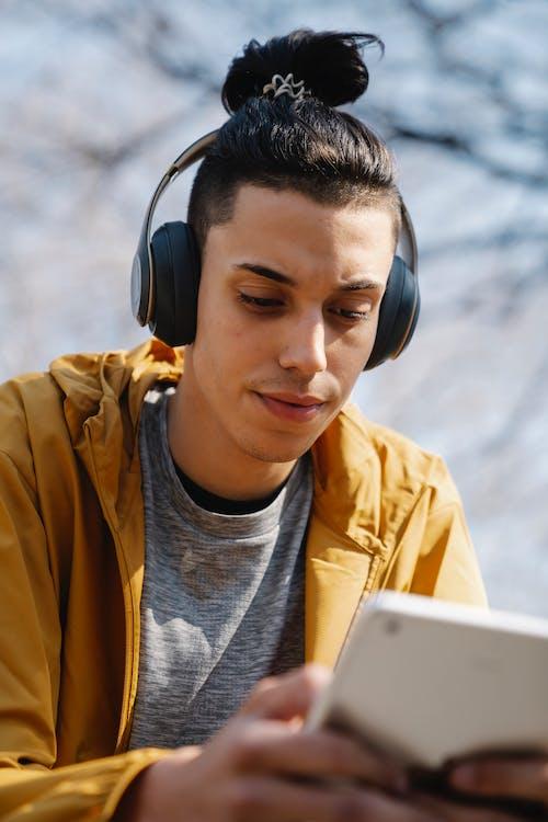 Ethnic man in headphones with smartphone on street