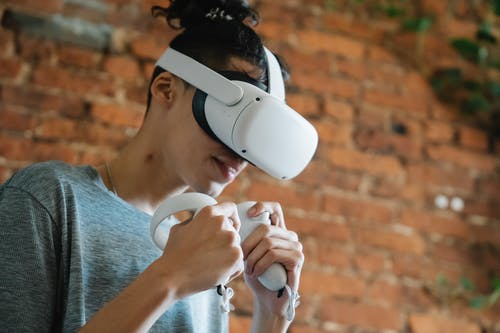 Gamer in VR headset playing video game against brick wall
