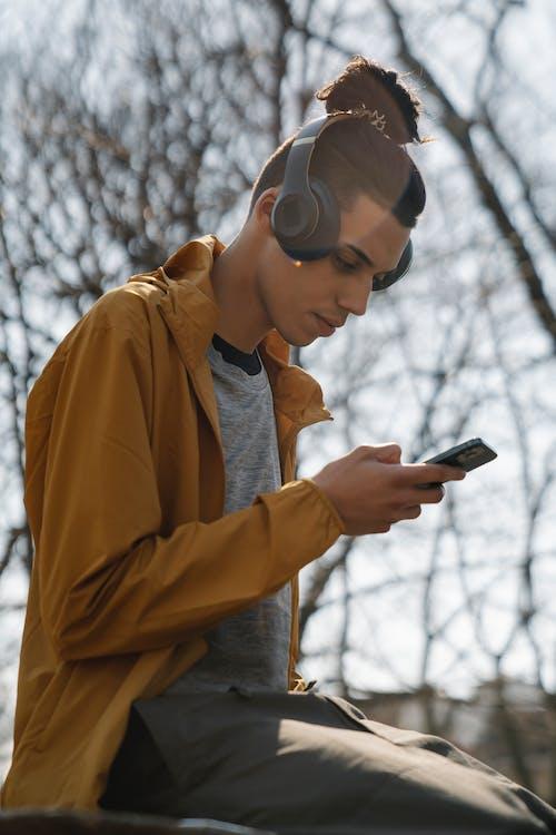 Man in Brown Jacket Holding Smartphone