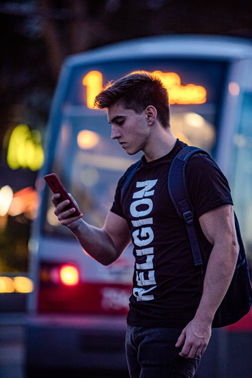 Man in Black and White Adidas Crew Neck T-shirt Holding Smartphone