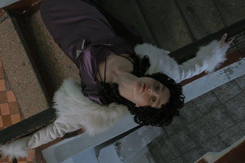 Elegant woman in dress leaning on stair handrail
