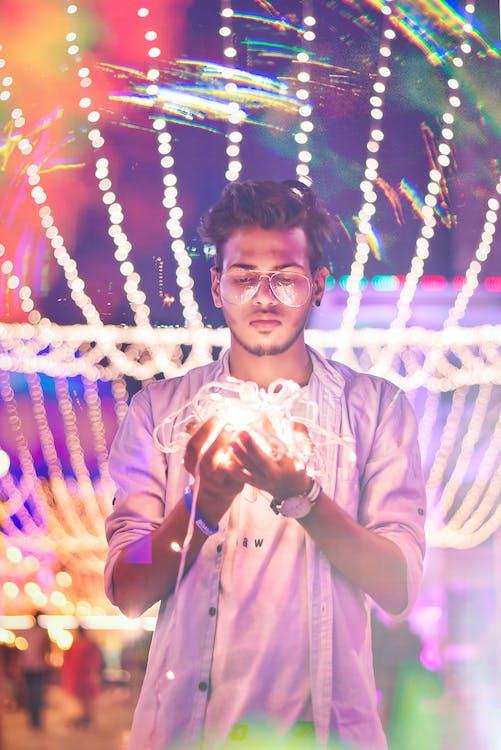 Man Holding String Light during Nighttime