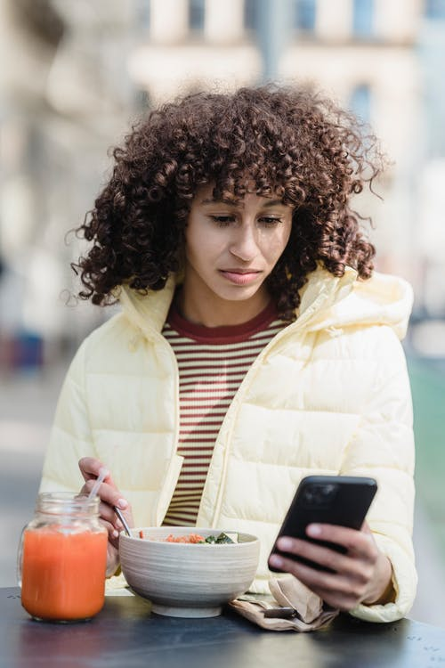 Ethnic woman with smartphone at cafe table with delicious meal