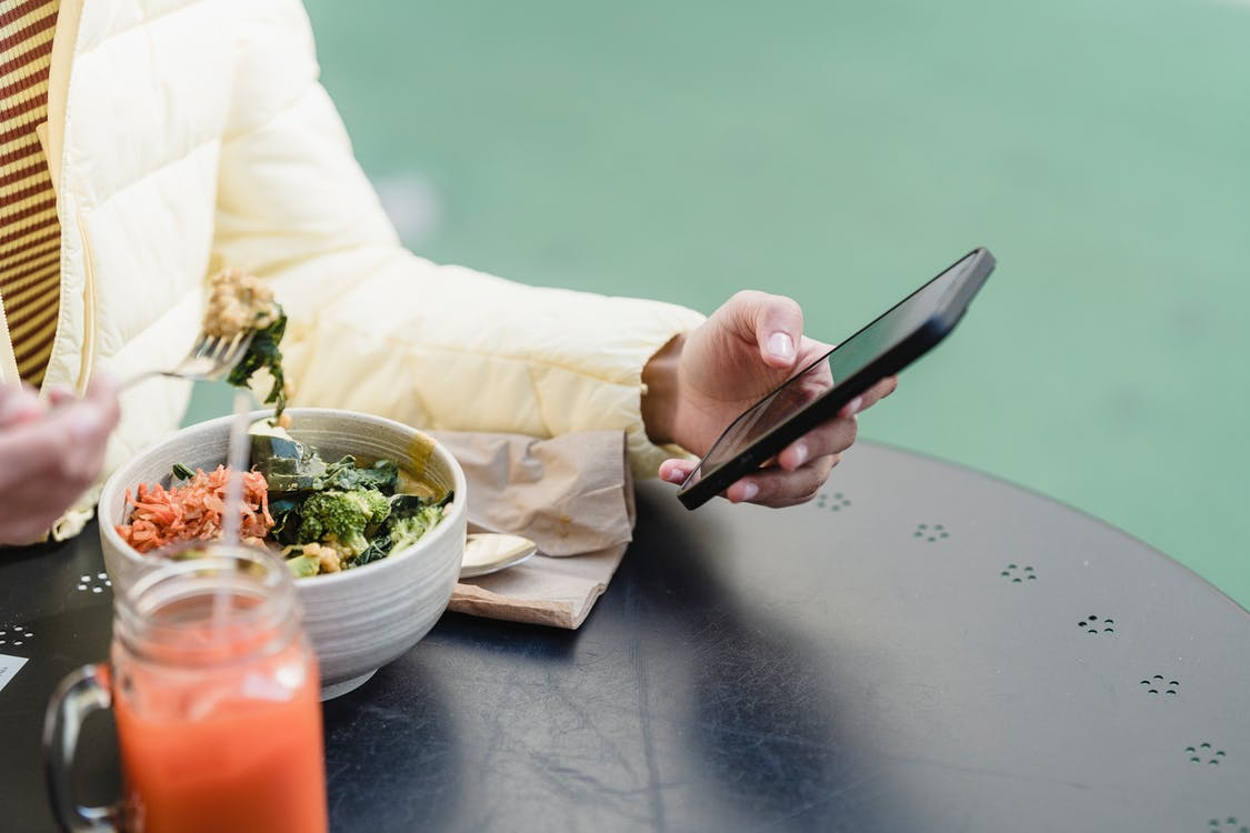 Crop woman with smartphone and vegetable salad in street cafeteria