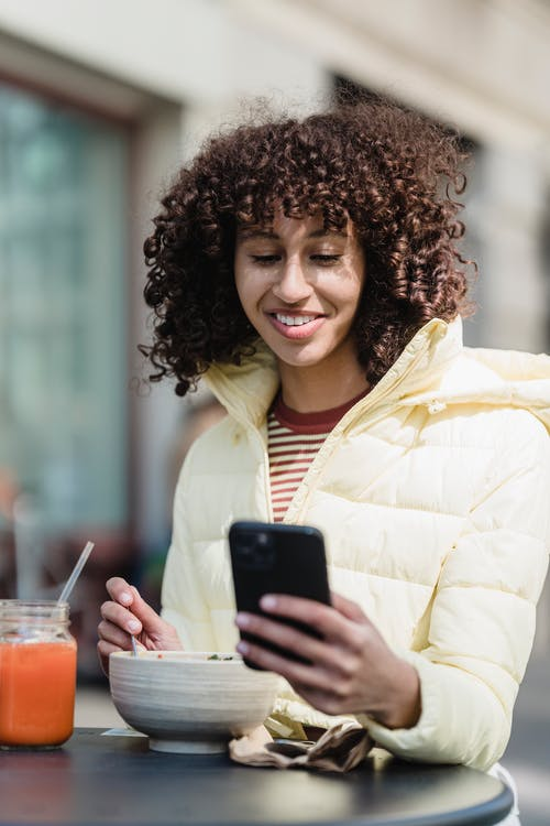 Cheerful ethnic woman with smartphone having lunch in street cafe