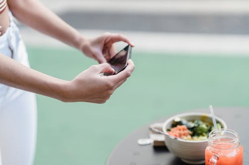 Crop unrecognizable female blogger taking photo of vegetable salad and smoothie on cellphone in street cafeteria