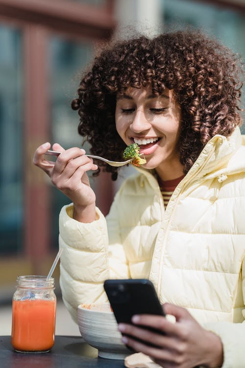 Smiling woman with smartphone eating broccoli in street cafeteria