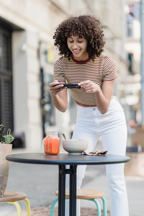 Cheerful ethnic female vlogger taking photo of food and smoothie on cellphone above cafeteria table in town