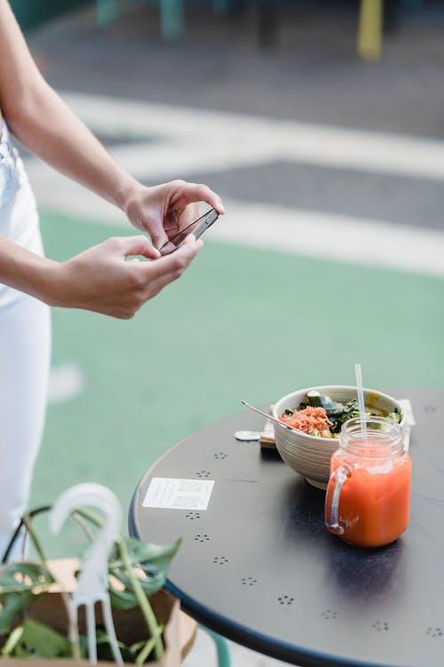 Faceless blogger taking photo of vegetarian food on smartphone