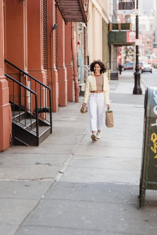 Content ethnic female buyer with paper bags strolling on tiled pavement while looking away in town