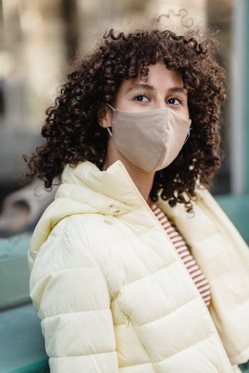Dreamy young ethnic female in padded jacket and cloth face mask looking away during COVID 19 pandemic in town
