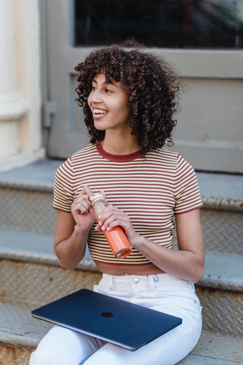Woman in White and Red Striped Crew Neck T-shirt Holding Orange Cup