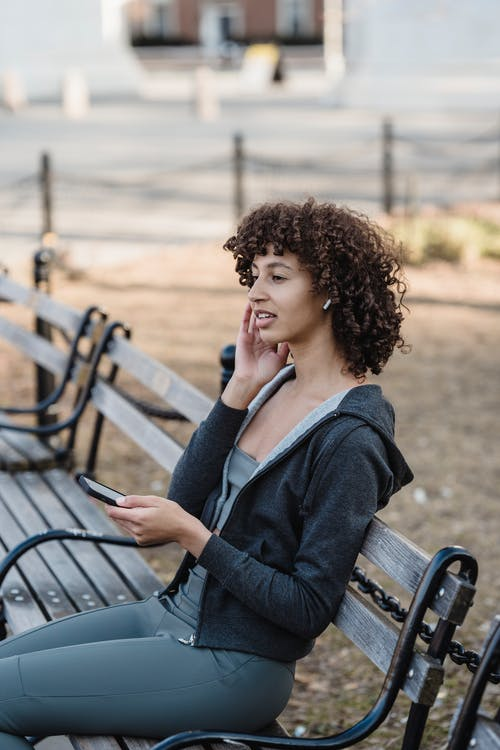 Woman in Blue Long Sleeve Shirt Sitting on Brown Wooden Bench
