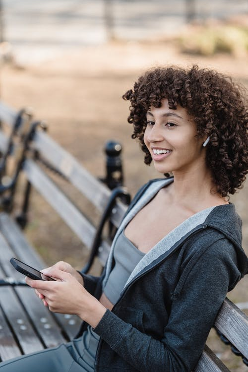 Cheerful ethnic woman in activewear with smartphone on bench