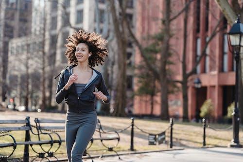 Positive ethnic woman running on city street