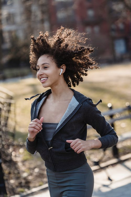 Smiling African American female with Afro hairstyle with wireless earphones running outside on blurred background
