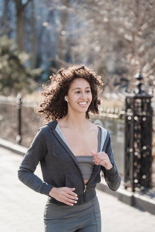 Smiling black woman walking on street