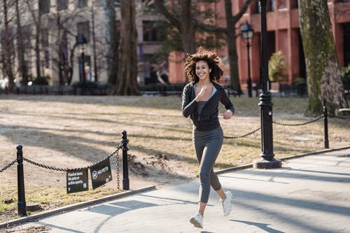 Full body of African American female jogger in sportswear smiling and running in park