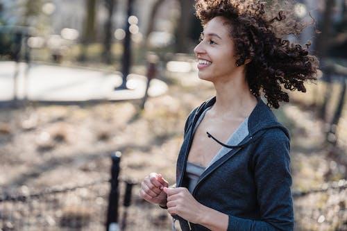 Positive black female jogging in park