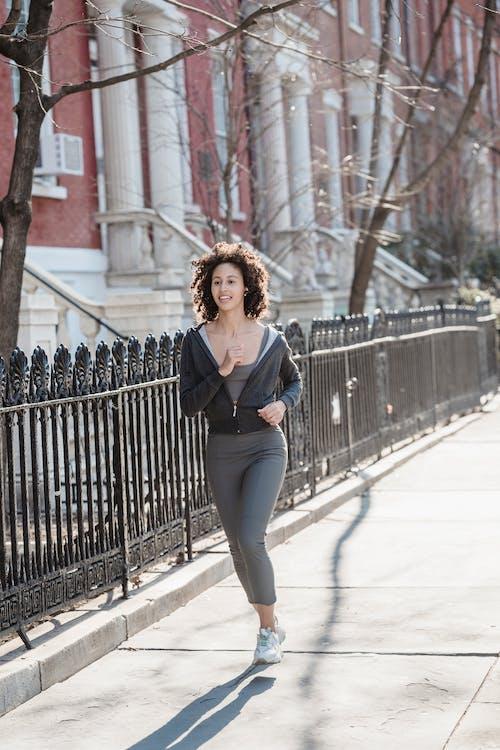 Full body of black female runner in sportswear jogging along iron fence in daylight