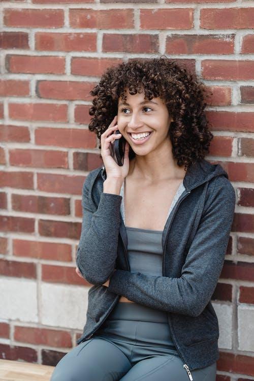 Cheerful black woman speaking on phone