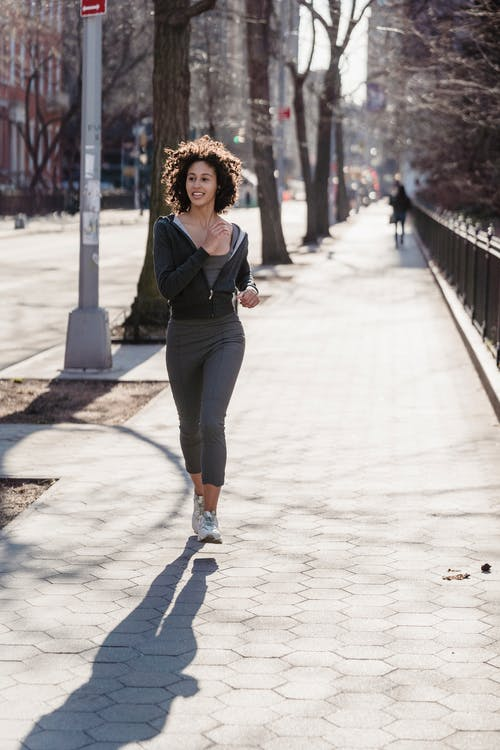 Full body of active young ethnic female millennial with dark curly hair in sportswear running on city street during morning workout on sunny day