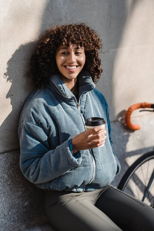 Cheerful ethnic woman with coffee to go on street