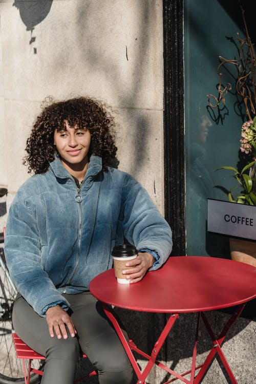 Contemplative ethnic female in jacket with paper cup of coffee looking away at urban cafeteria table on sunny day