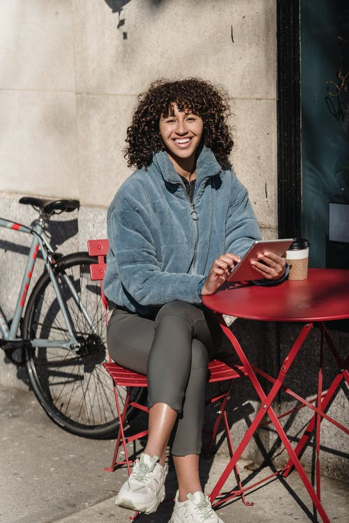 Cheerful ethnic female with cellphone and takeaway hot drink sitting with crossed legs at urban cafe table while looking at camera