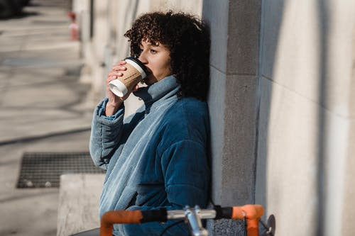 Side view of dreamy young ethnic female enjoying hot drink from paper cup while looking away in sunny town