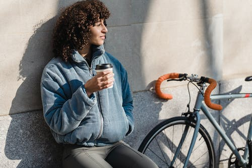 Pondering young ethnic female with hand in pocket and disposable glass of hot beverage looking away against bicycle in town