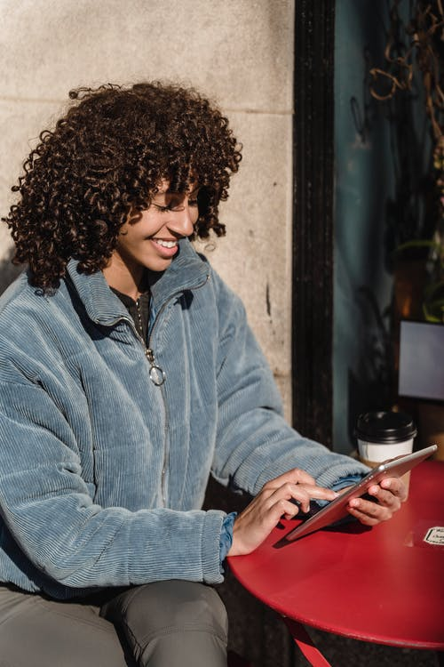 Cheerful ethnic woman touching screen on smartphone in urban cafeteria