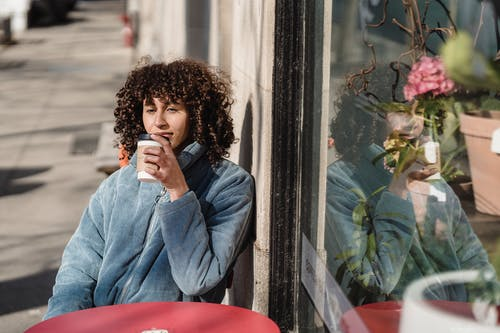 Dreamy young ethnic female with takeaway hot drink looking away at urban cafeteria table while reflecting in glass wall