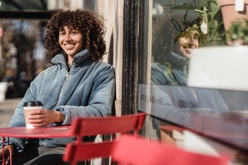 Happy ethnic woman with takeaway coffee in street cafeteria
