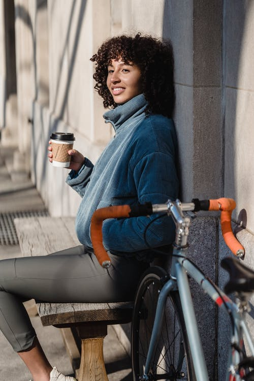 Smiling ethnic woman with coffee to go on street bench