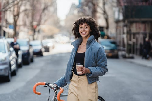 Smiling ethnic woman with coffee and bike on urban road