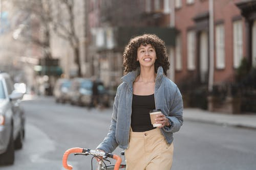 Cheerful young ethnic woman with and coffee in city