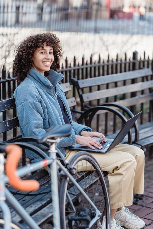 Positive young ethnic female freelancer with curly hair in trendy warm jacket smiling and looking at camera while browsing laptop sitting on wooden bench in city park