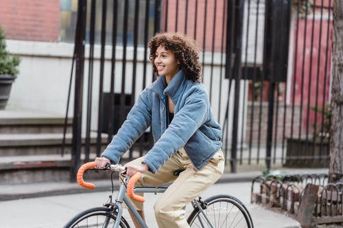 Happy ethnic young trendy female in blue jacket smiling while riding bicycle on city street in autumn
