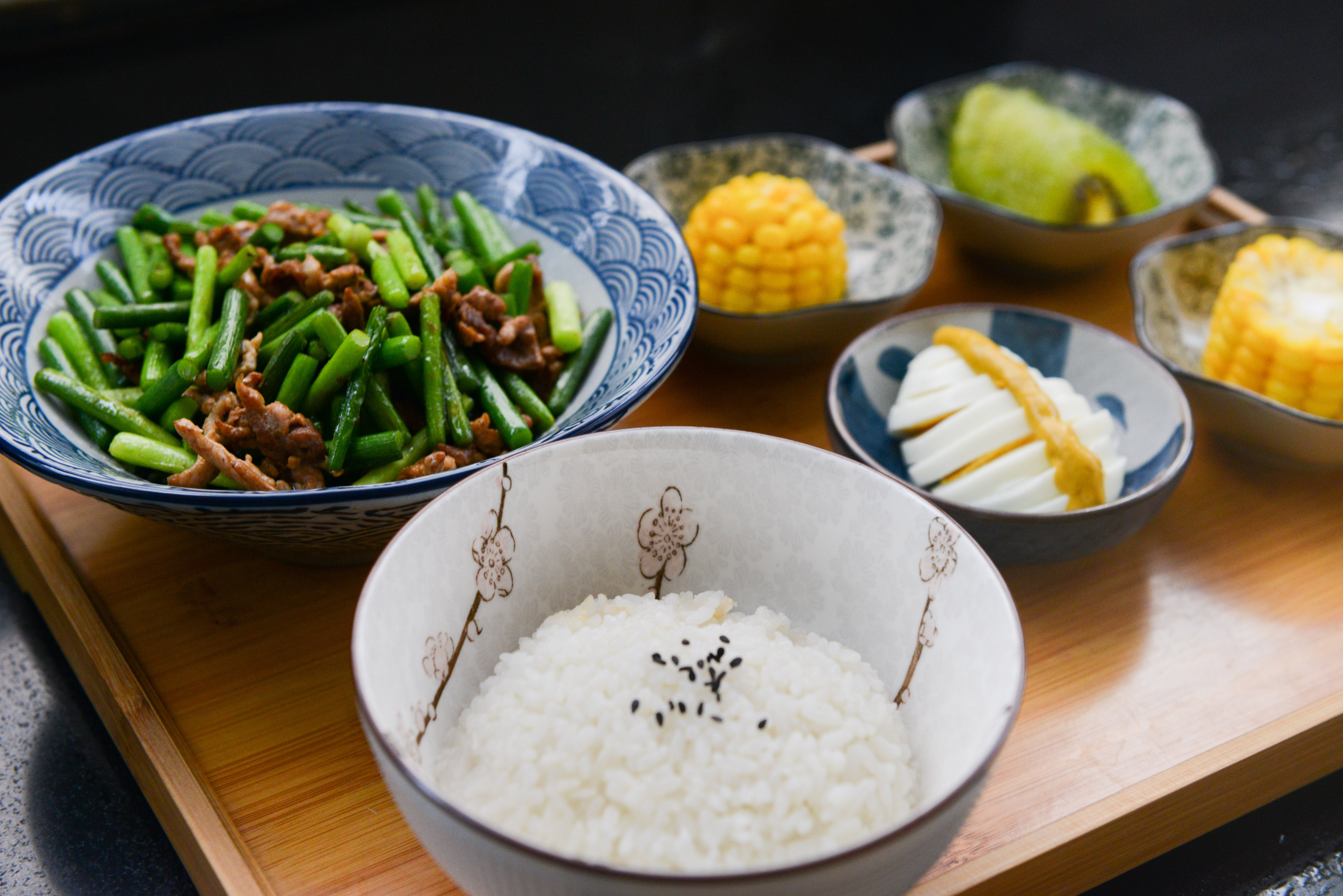 Rice on Bowl, Sliced-egg, Corn, and Vegetable on Table