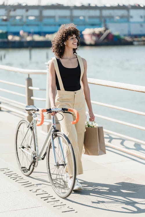 Cheerful woman with bicycle and shopping bag on embankment