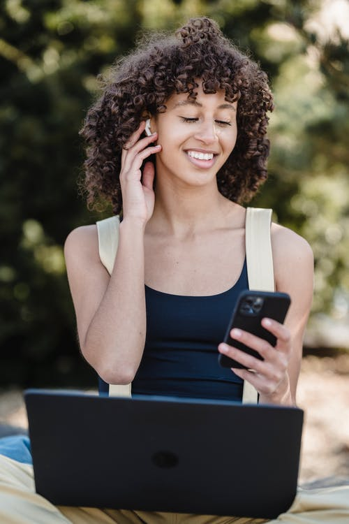 Cheerful African American female sitting in park with laptop and listening music from smartphone using wireless earbuds