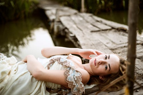 Woman in Brown and White Floral Dress Lying on Brown Wooden Dock