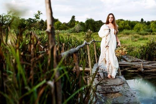 Woman in White Dress Sitting on Brown Wooden Bridge
