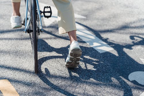 Crop person riding bicycle on street