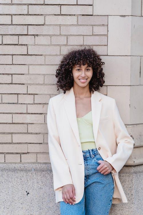 Stylish black woman smiling while standing near brick wall