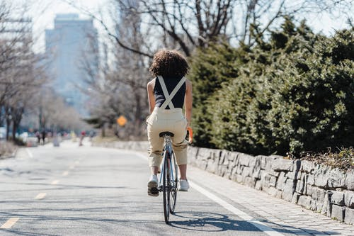 Back view of black anonymous female cyclist riding bicycle on asphalt road in city with green lush bushes aside