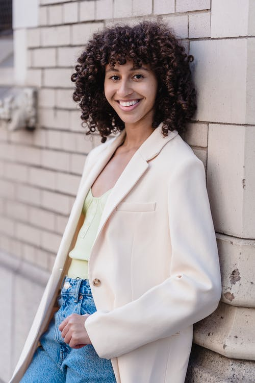 Smiling African American female leaning on brick wall