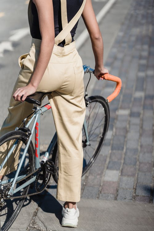 Unrecognizable ethnic female siting on bicycle on street