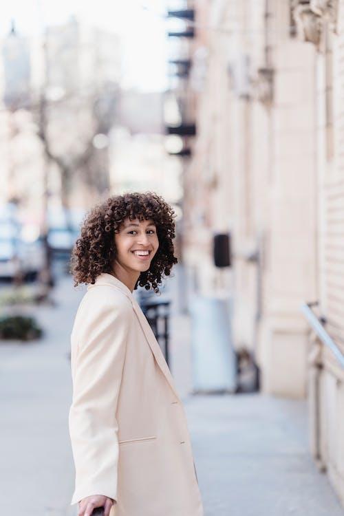Smiling black woman in jacket standing on street